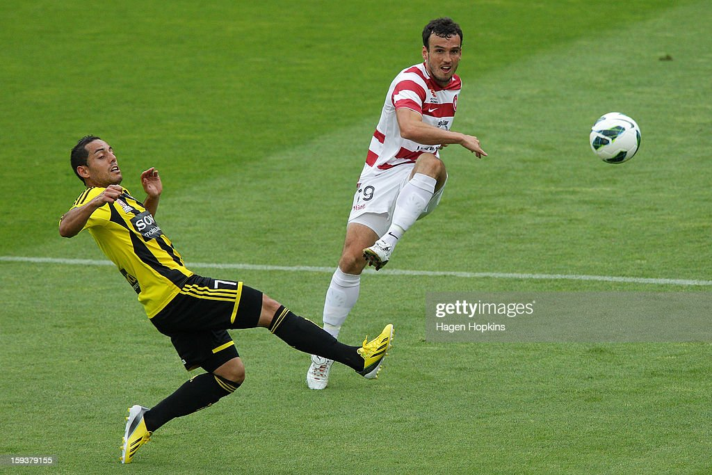 Mark Bridge of the Wanderers takes a shot at goal past the defence of Leo Bertos of the Phoenix during the round 16 A-League match between the Wellington Phoenix and the Western Sydney Wanderers at Westpac Stadium on January 13, 2013 in Wellington, New Zealand.