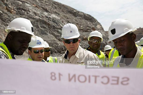 Mark Bristow chief executive officer of Randgold Resources Ltd center looks at plans with his management team during a tour of the open pit gold mine...