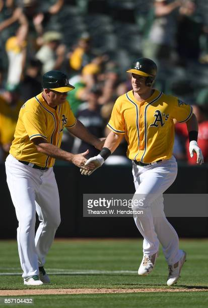 Mark Canha of the Oakland Athletics is congratulated by third base coache Steve Scarsone after Canha hit a walkoff solo home run to defeat the...