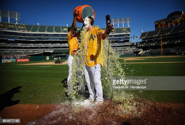 Mark Canha of the Oakland Athletics is showered with Gatorade by teammate Marcus Semien after Canha hit a walkoff solo home run to defeat the Seattle...