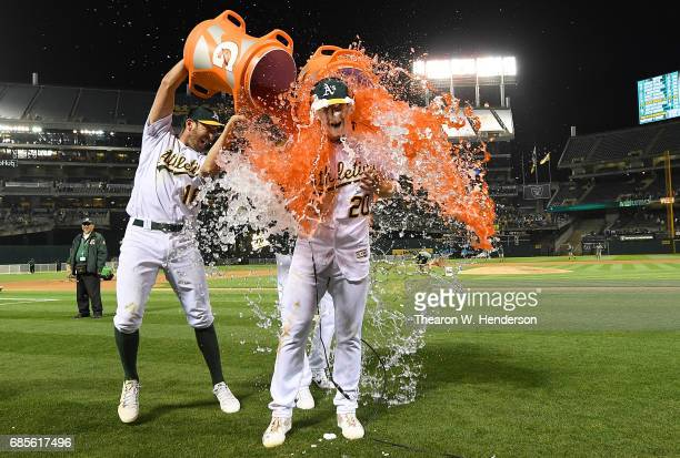 Mark Canha of the Oakland Athletics is soaked with gatorade by Adam Rosales after Canha hit a walk off solo home run to defeat the Boston Red Sox 32...