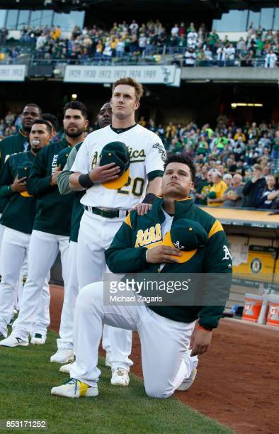 Mark Canha of the Oakland Athletics puts his hand on the should of Bruce Maxwell as Maxwell kneels during the anthem prior to the game against the...