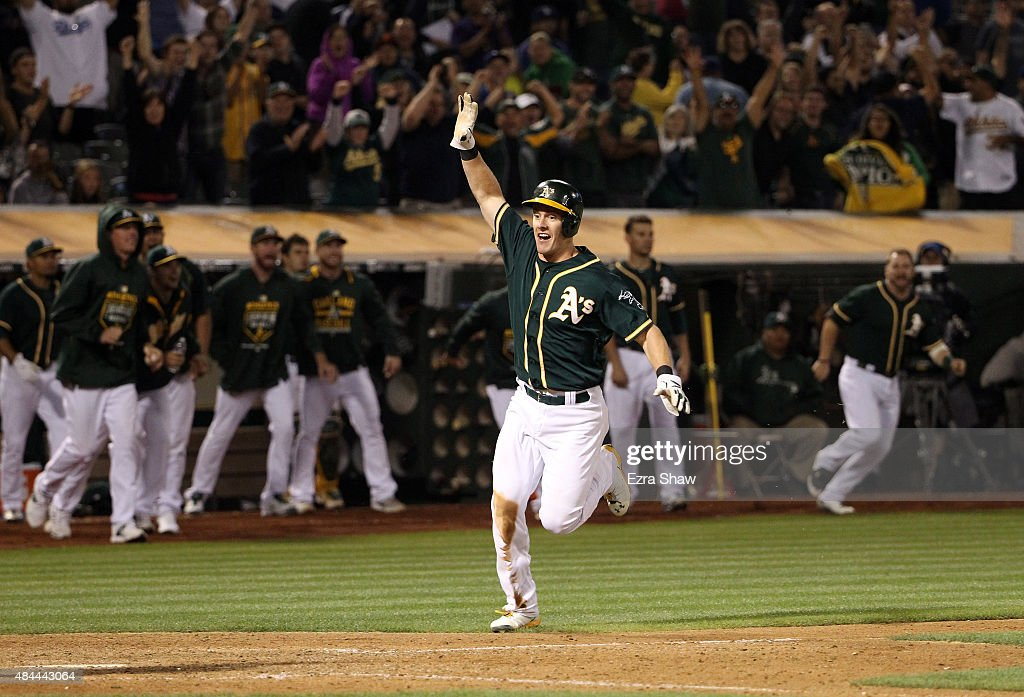 <a gi-track='captionPersonalityLinkClicked' href=/galleries/search?phrase=Mark+Canha&family=editorial&specificpeople=12504968 ng-click='$event.stopPropagation()'>Mark Canha</a> #20 of the Oakland Athletics runs home to score the winning run on a hit by <a gi-track='captionPersonalityLinkClicked' href=/galleries/search?phrase=Billy+Butler&family=editorial&specificpeople=759092 ng-click='$event.stopPropagation()'>Billy Butler</a> #16 in the 10th inning of their game against the Los Angeles Dodgers at O.co Coliseum on August 18, 2015 in Oakland, California.