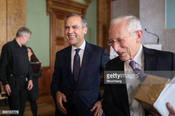 Mark Carney governor of the Bank of England center reacts after Stanley Fischer vice chairman of the US Federal Reserve delivered a speech during the...
