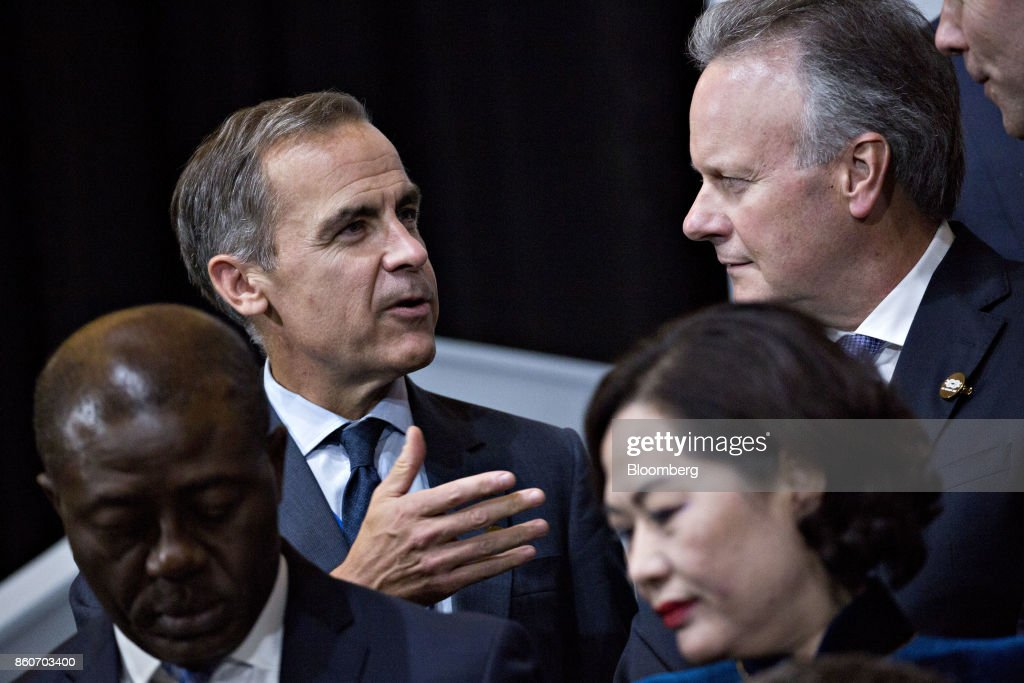 Mark Carney, governor of the Bank of England, left, talks to Stephen Poloz, governor of the Bank of Canada, during a Group of 20 (G-20) finance ministers and central bank governors group photo on the sidelines of the International Monetary Fund (IMF) and World Bank Group Annual Meetings in Washington, D.C., U.S., on Thursday, Oct. 12, 2017. Near-term risks to world financial stability have declined since April amid improving macroeconomic conditions and the subsiding risk of emerging-market turmoil, the IMF said in its latest Global Financial Stability Report released yesterday. Photographer: Andrew Harrer/Bloomberg via Getty Images