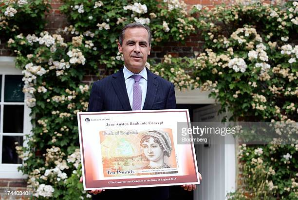 Mark Carney governor of the Bank of England stands holding the concept design for the new Bank of England ten pound banknote featuring author Jane...