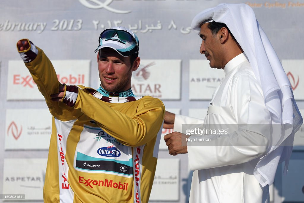 Mark Cavendish of Great Britain and Omega Pharma - Quick Step pulls on the race leaders gold jersey after winning stage four of the Tour of Qatar from Camel Race Track to Al Khor Corniche on February 6, 2013 in Al Khor Corniche, Qatar.