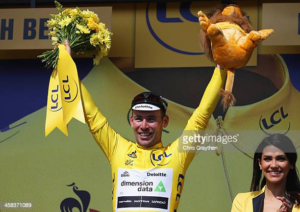 Mark Cavendish of Great Britain and Team Dimension Data celebrates in the yellow jersey on the podum after victory during Stage One of Le Tour de...