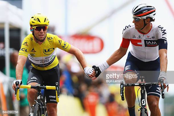 Mark Cavendish of Great Britain Team Dimension Data shakes hands with Reto Hollenstein of Switzerland and IAM Cycling at the end of stage two of the...