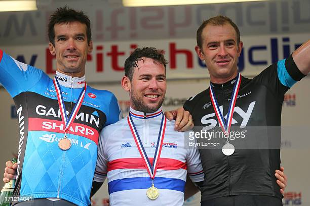 Mark Cavendish of Omega PharmaQuickstep celebrates on the podium after winning the 2013 National Mens Road Race Championships alongside third placed...