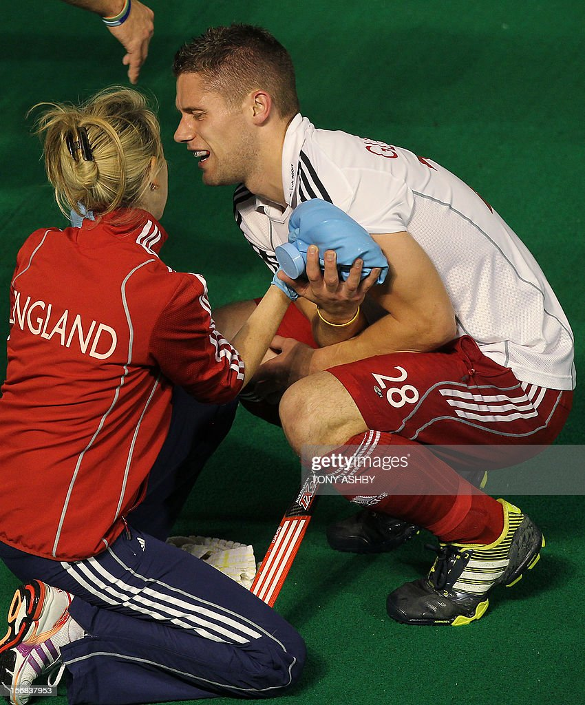 Mark Cleghorne of England (R) suffers an injured shoulder after clashing with Singh Sardar of India during their mens match at the International Super Series hockey tournament in Perth on November 22, 2012. AFP PHOTO / Tony ASHBY RESTRICTED