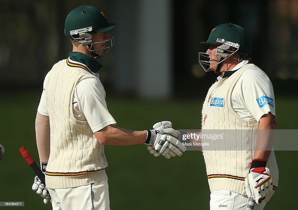 Mark Cosgrove and Jordan Silk of the Tigers shake hands to celebrate a 100 run partnership during day one of the Sheffield Shield final between the Tasmania Tigers and the Queensland Bulls at Blundstone Arena on March 22, 2013 in Hobart, Australia.