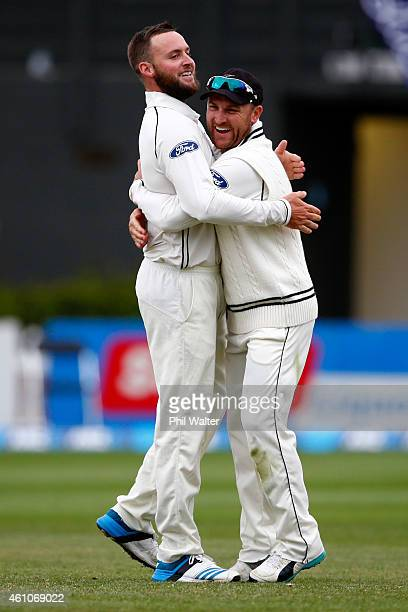 Mark Craig of New Zealand is hugged by Brendon McCullum after taking the wicket of Dimuth Karunaratne of Sri Lanka during day four of the Second Test...