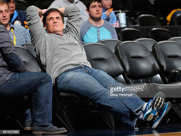 Mark Cuban owner of the Dallas Mavericks sits courtside as his team warms up prior to facing the Denver Nuggets at Pepsi Center on January 14 2015 in...