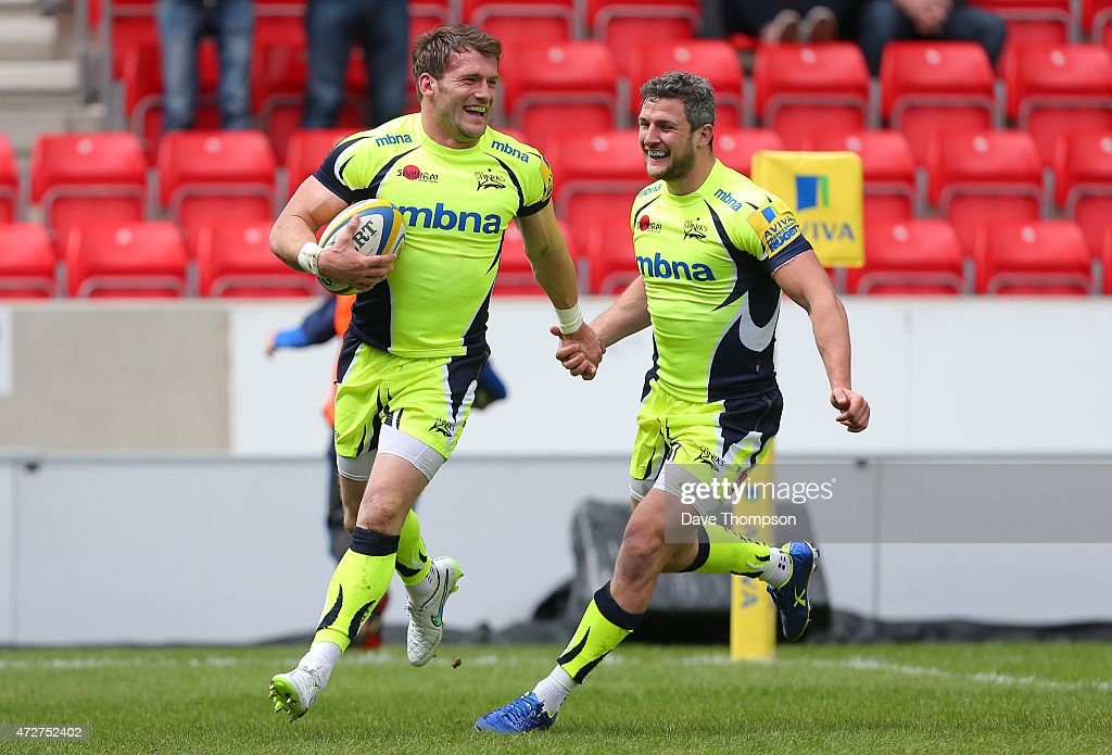 Mark Cueto of Sale Sharks celebrates with team mate Tom Brady as he crosses the line to score a try during the Aviva Premiership match between Sale Sharks and Newcastle Falcons at the AJ Bell Stadium on May 9, 2015 in Salford, England.