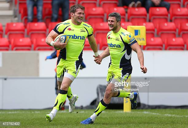 Mark Cueto of Sale Sharks celebrates with team mate Tom Brady as he crosses the line to score a try during the Aviva Premiership match between Sale...