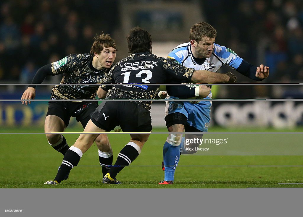 Mark Cueto of Sale Sharks is tackled by Thomas Combezou of Montpellier during the Heineken Cup Pool 6 match between Sale Sharks and Montpellier at Salford City Stadium on January 11, 2013 in Salford, England.