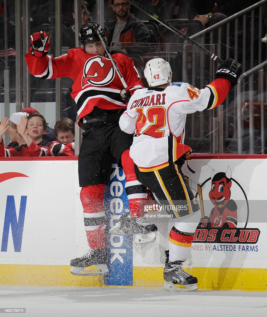 Mark Cundari #42 of the Calgary Flames hits Steve Bernier #18 of the New Jersey Devils into the boards during the second period at the Prudential Center on April 7, 2014 in Newark, New Jersey.