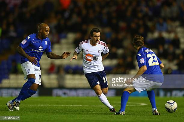 Mark Davies of Bolton Wanderers passes as Marlon King and Jonathan Spector of Birmingham City close in during the npower Championship match between...