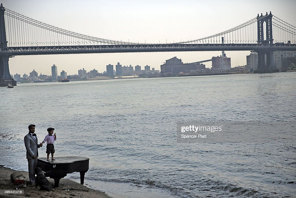 Mark Deliz and his son Sebastion, 3, pause at a piano underneath the Brooklyn Bridge on June 3, 2014 in New York City. A grand piano that has mysteriously landed on a sliver of beach under the iconic bridge last week has become an impromptu tourist attraction. While the Mason & Hamlin piano is badly damaged, dozens of people climb onto the beach daily to test out the keys.