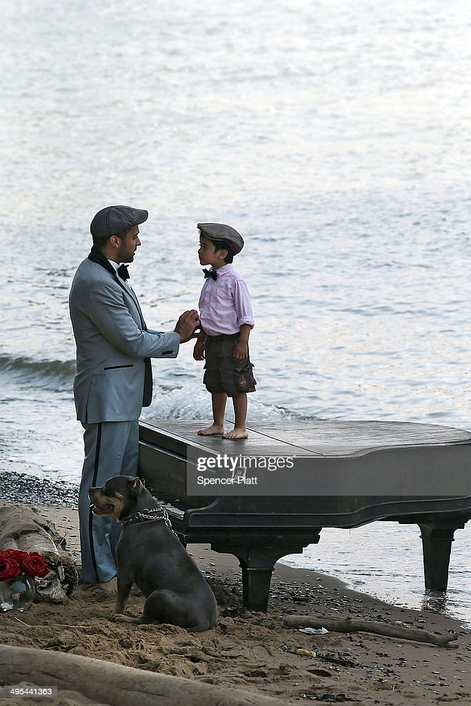 Mark Deliz and his son Sebastion, 3, pause with their dog Bruno at a piano underneath the Brooklyn Bridge on June 3, 2014 in New York City. A grand piano that has mysteriously landed on a sliver of beach under the iconic bridge last week has become an impromptu tourist attraction. While the Mason & Hamlin piano is badly damaged, dozens of people climb onto the beach daily to test out the keys.