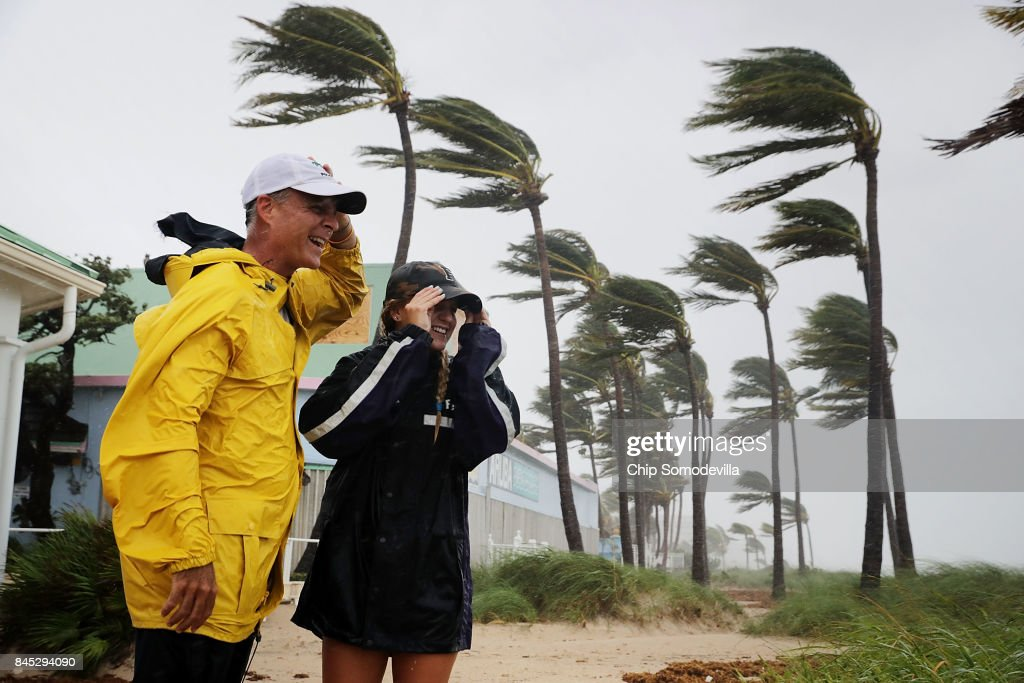 Mark Depenbrock (L) and his daughter Chloe Depenbrock brace against tropical storm strength winds on the beach near Anglins Fishing Pier as Hurricane Irma hits the southern part of the state September 10, 2017 in Fort Lauderdale, Florida. The Category 4 hurricane made landfall in the United States in the Florida Keys at 9:10 a.m. after raking across the north coast of Cuba.