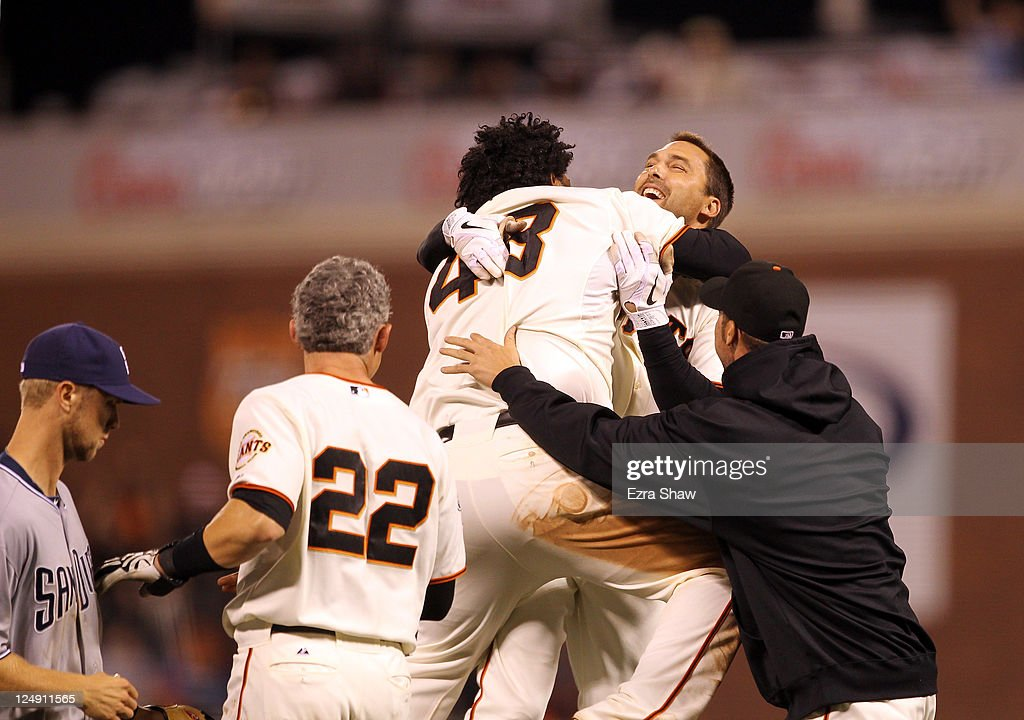 Mark DeRosa #7 of the San Francisco Giants is congratulated by teammates after hitting the game winning hit in the bottom of the 12th inning against the San Diego Padres at AT&T Park on September 13, 2011 in San Francisco, California.