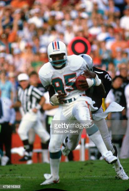 Mark Duper of the Miami Dolphins runs with the ball after a catch against the Los Angeles Raiders during an NFL football game circa 1984 at the...