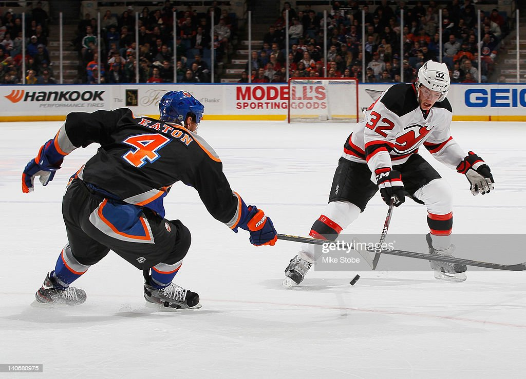 Mark Eaton #4 of the New York Islanders gets his stick in the way of Matt Taormina #32 of the New Jersey Devils at Nassau Veterans Memorial Coliseum on March 4, 2012 in Uniondale, New York.