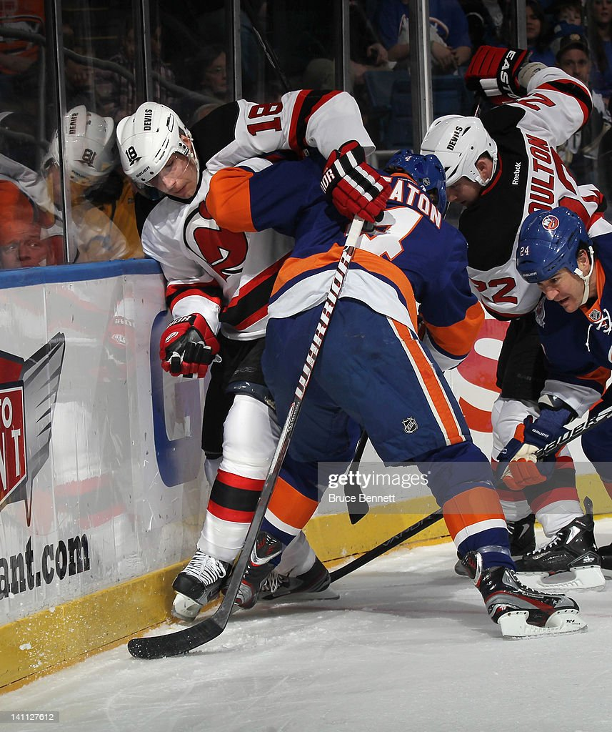 Mark Eaton #4 of the New York Islanders holds Steve Bernier #18 of the New Jersey Devils against the boards at the Nassau Veterans Memorial Coliseum on March 10, 2012 in Uniondale, New York.