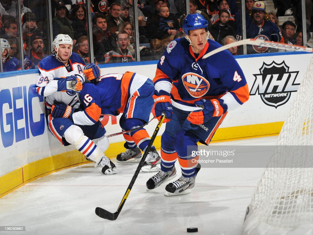 Mark Eaton #4 of the New York Islanders skates away with the puck as teammate Marty Reasoner #16 checks Ryan Smyth #94 of the Edmonton Oilers hard into the boards at Nassau Veterans Memorial Coliseum on December 31, 2011 in Uniondale, New York.