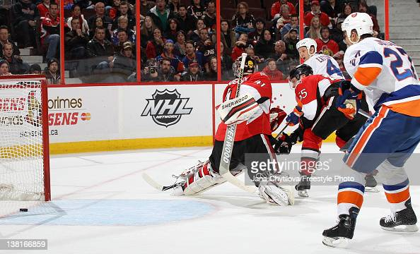 Mark Eaton of the New York Islanders watches his game winning overtime goal get past Craig Anderson of the Ottawa Senators during an NHL game at...