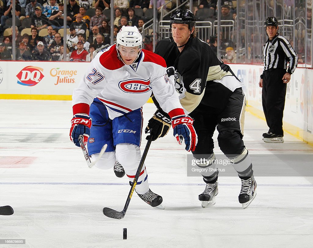Mark Eaton #4 of the Pittsburgh Penguins skates for the loose puck alongside Alex Galchenyuk #27 of the Montreal Canadiens on April17, 2013 at Consol Energy Center in Pittsburgh, Pennsylvania.