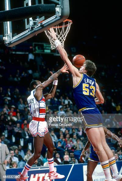 Mark Eaton of the Utah Jazz attempts to block the pass of Gus Williams of the Washington Bullets during an NBA basketball game circa 1985 at the...