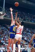 Mark Eaton of the Utah Jazz attempts to block the shot of John Lucas of the Houston Rockets during an NBA basketball game circa 1984 at The Summit in...