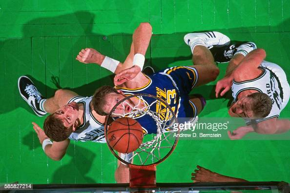 Mark Eaton of the Utah Jazz boxes out Joe Kleine and Larry Bird of the Boston Celtics during a game at the Boston Garden in Boston Massachusetts...