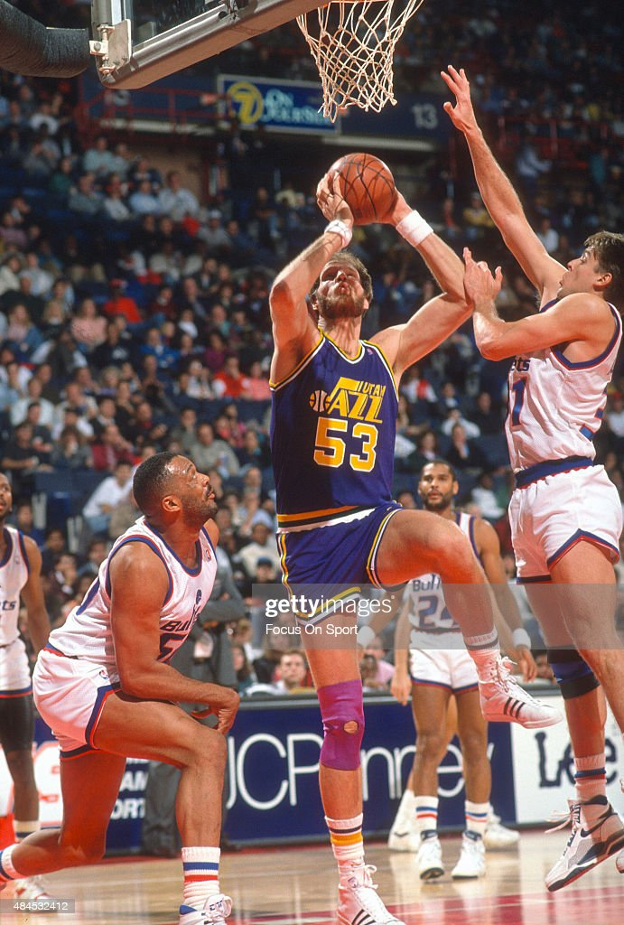 Mark Eaton of the Utah Jazz goes up to shoot over Mark Alarie of the Washington Bullets during an NBA basketball game circa 1989 at the Capital...
