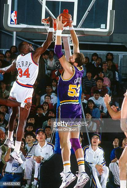 Mark Eaton of the Utah Jazz grabs a rebound away from Tim Perry of the Phoenix Suns during an NBA basketball game circa 1990 at the Arizona Veterans...