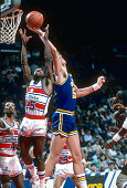 Mark Eaton of the Utah Jazz grabs a rebound over Frank Johnson of the Washington Bullets during an NBA basketball game circa 1986 at the Capital...