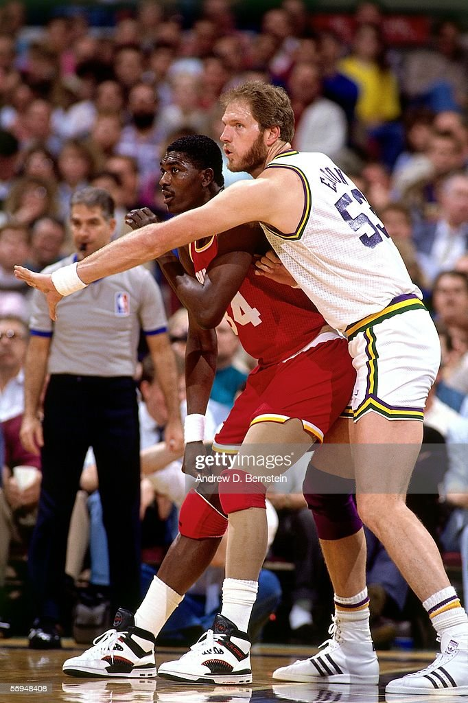 Mark Eaton #53 of the Utah Jazz guards Hakeem Olajuwon #34 of the Houston Rockets in the post during an NBA game circa 1989 in Salt Lake City, Utah.