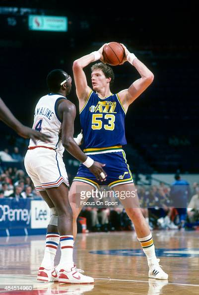 Mark Eaton of the Utah Jazz looks to pass the ball over the top of Moses Malone of the Washington Bullets during an NBA basketball game circa 1986 at...