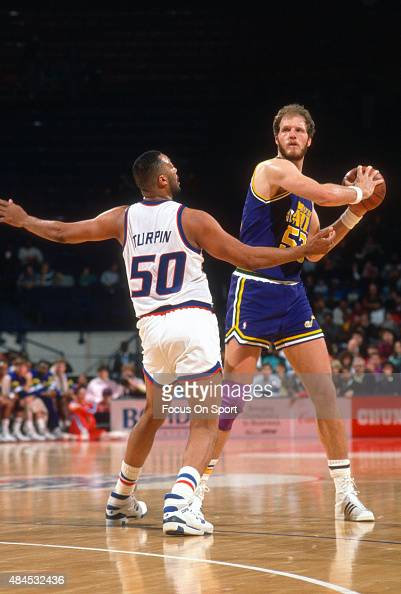 Mark Eaton of the Utah Jazz looks to pass the ball over the top of Melvin Turpin of the Washington Bullets during an NBA basketball game circa 1989...