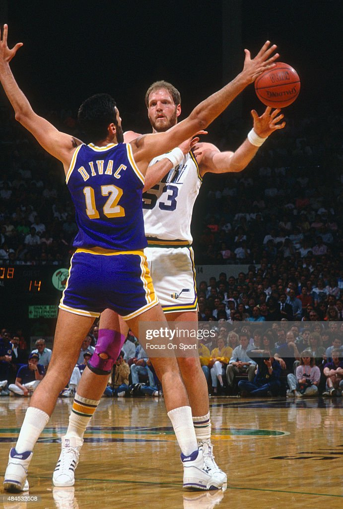 Mark Eaton of the Utah Jazz passes the ball by Vlade Divac of the Los Angeles Lakers during an NBA basketball game circa 1990 at the Salt Palace in...
