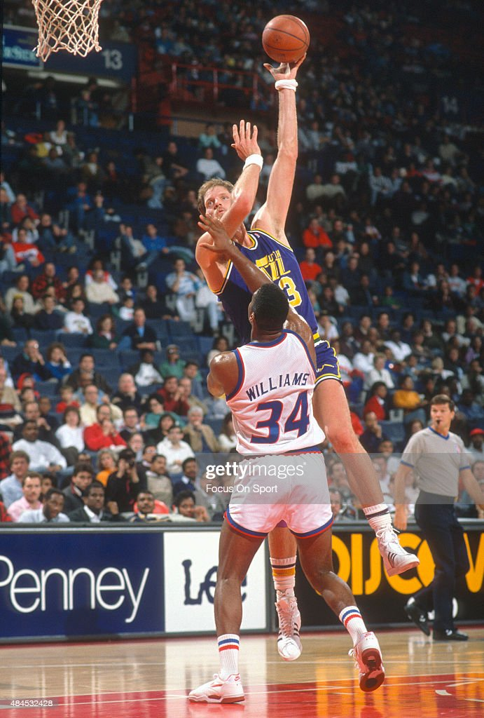 Mark Eaton of the Utah Jazz shoots over John Williams of the Washington Bullets during an NBA basketball game circa 1989 at the Capital Centre in...