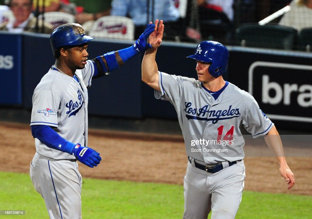 Mark Ellis #14 and Hanley Ramirez #13 of the Los Angeles Dodgers celebrate after a two-run home run by Ramirez in the eighth inning against the Atlanta Braves during Game Two of the National League Division Series at Turner Field on October 4, 2013 in Atlanta, Georgia.