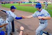 Mark Ellis celebrates with manager Don Mattingly of the Los Angeles Dodgers and teammates after scoring in the first inning against the Atlanta...