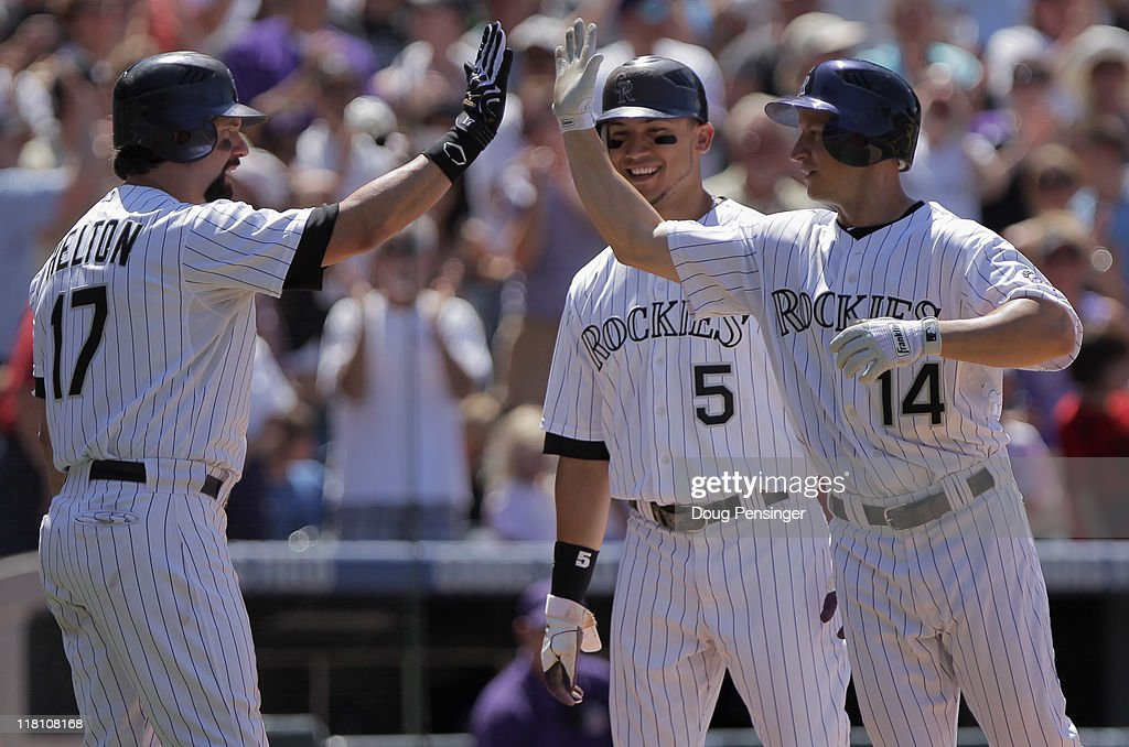 Mark Ellis #14 of the Colorado Rockies is congratulated for his homerun by Todd Helton #17 and Carlos Gonzalez #5 of the Colorado Rockies in the fifth inning against the Kansas City Royals during Interleague play at Coors Field on July 3, 2011 in Denver, Colorado. The Royals defeated the Rockies 16-8.