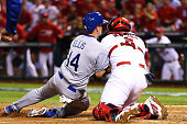 Mark Ellis of the Los Angeles Dodgers is out at home plate in the 10th inning against Yadier Molina of the St Louis Cardinals during Game One of the...
