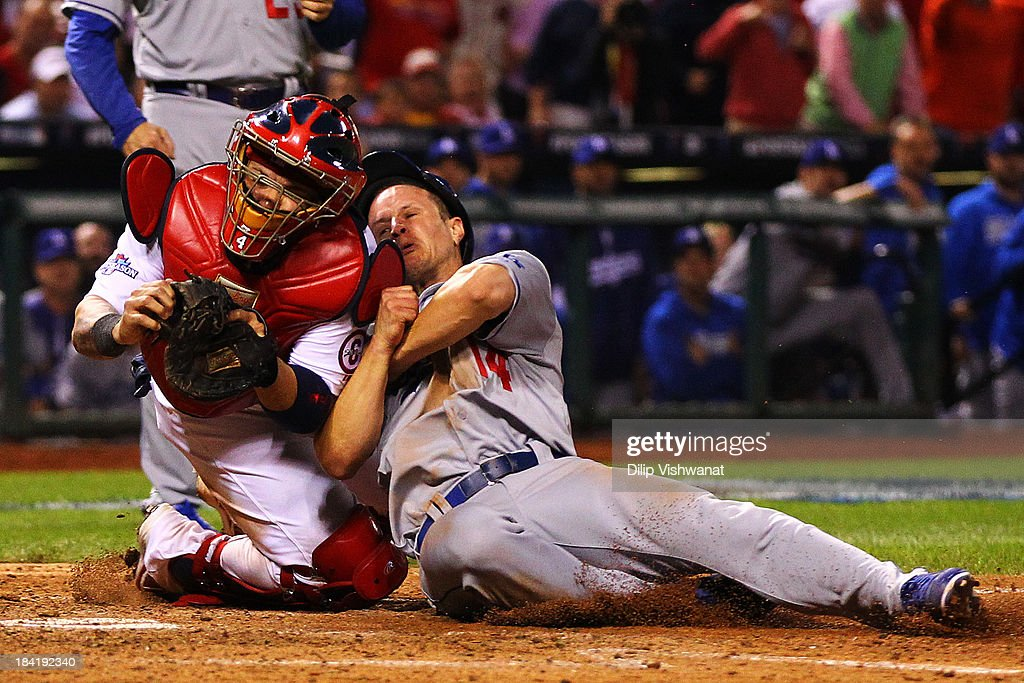 Mark Ellis #14 of the Los Angeles Dodgers is out at home plate in the 10th inning against Yadier Molina #4 of the St. Louis Cardinals during Game One of the National League Championship Series at Busch Stadium on October 11, 2013 in St Louis, Missouri.