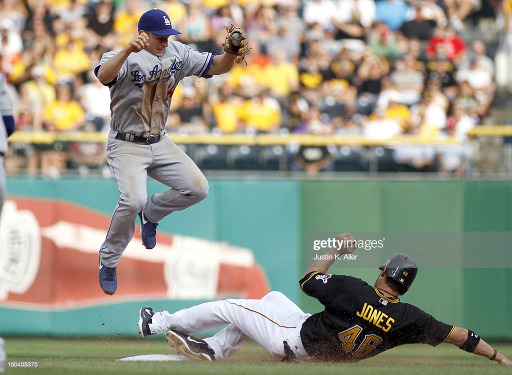 <a gi-track='captionPersonalityLinkClicked' href=/galleries/search?phrase=Mark+Ellis+-+Baseball+Player&family=editorial&specificpeople=213759 ng-click='$event.stopPropagation()'>Mark Ellis</a> #14 of the Los Angeles Dodgers jumps in the air as <a gi-track='captionPersonalityLinkClicked' href=/galleries/search?phrase=Garrett+Jones&family=editorial&specificpeople=835861 ng-click='$event.stopPropagation()'>Garrett Jones</a> #46 of the Pittsburgh Pirates slides during the game on August 16, 2012 at PNC Park in Pittsburgh, Pennsylvania. The Pirates defeated the Dodgers 10-6.